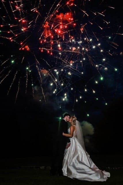 Fireworks are running behind bride and groom